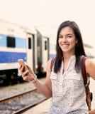 Studente millenario sicuro in movimento che controlla il suo Smart Phone su un binario del treno Immagine Stock