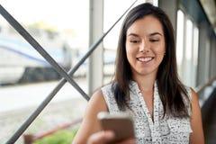 Studente millenario sicuro in movimento che controlla il suo Smart Phone su un binario del treno Immagini Stock Libere da Diritti