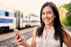 Studente millenario sicuro in movimento che controlla il suo Smart Phone su un binario del treno Immagini Stock