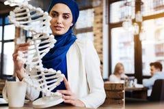 Studente musulmano femminile curioso che tiene il modello del DNA Immagine Stock Libera da Diritti