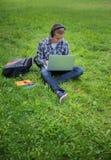 Studente nel parco della città universitaria che studia sul computer portatile Immagine Stock Libera da Diritti