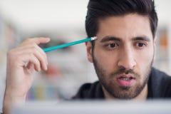 Studente nella biblioteca di scuola facendo uso del computer portatile per ricerca Fotografia Stock Libera da Diritti