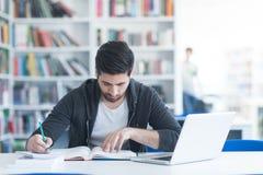 Studente nella biblioteca di scuola facendo uso del computer portatile per ricerca Immagine Stock Libera da Diritti