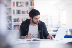 Studente nella biblioteca di scuola facendo uso del computer portatile per ricerca Immagini Stock