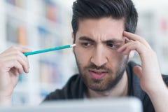 Studente nella biblioteca di scuola facendo uso del computer portatile per ricerca Immagine Stock
