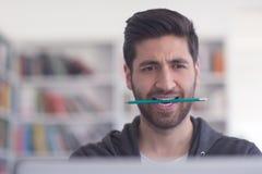 Studente nella biblioteca di scuola facendo uso del computer portatile per ricerca Immagini Stock Libere da Diritti