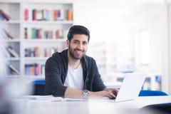Studente nella biblioteca di scuola facendo uso del computer portatile per ricerca Fotografia Stock