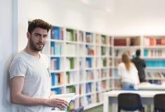 Studente nella biblioteca di scuola facendo uso della compressa per ricerca Immagine Stock Libera da Diritti