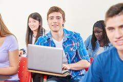Studente nella classe con un computer portatile Fotografie Stock