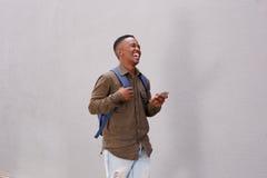 Studente nero sorridente che cammina con il cellulare e la borsa Immagine Stock Libera da Diritti