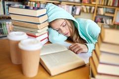 Studente o donna con i libri che dorme nella biblioteca Immagine Stock