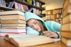 Studente o donna con i libri che dorme nella biblioteca Immagine Stock Libera da Diritti