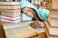 Studente o donna con i libri che dorme nella biblioteca Fotografie Stock Libere da Diritti