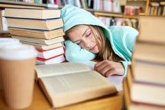 Studente o donna con i libri che dorme nella biblioteca Immagini Stock