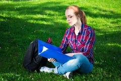 Studente o ragazza adolescente della scuola che si siede nel parco Immagini Stock