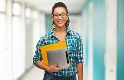 Studente in occhiali con le cartelle ed il pc della compressa Fotografia Stock