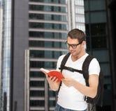 Studente in occhiali con lo zaino ed il libro Fotografie Stock