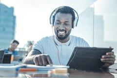 Studente occupato di positivo che studia e che ascolta la musica Fotografia Stock