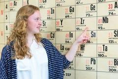 Studente olandese femminile che indica al grafico della parete con la tavola periodica Fotografia Stock Libera da Diritti