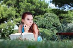 Studente in parco con il libro aperto Immagini Stock