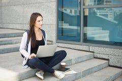Studente pensieroso che si siede sulle scale facendo uso del computer portatile Immagini Stock Libere da Diritti