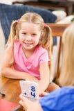 Studente: Per la matematica di pratica sorridente della ragazza con i flash card Immagine Stock Libera da Diritti
