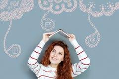 Studente positivo che sorride mentre mettendo un libro sopra la sua testa Immagini Stock