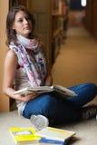 Studente premuroso che si siede con i libri nella biblioteca Immagini Stock