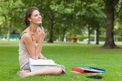 Studente premuroso con i libri che si siedono al parco Immagine Stock Libera da Diritti