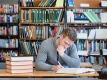 Studente premuroso con il libro aperto che lavora in una biblioteca Immagini Stock Libere da Diritti