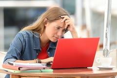 Studente preoccupato che cerca sulla linea in un computer portatile Immagine Stock Libera da Diritti