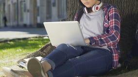 Studente razza mista che fa il suo progetto del diploma che si siede con il computer portatile all'aperto archivi video
