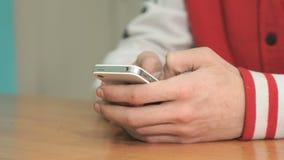 Studente sconosciuto che tiene smartphone bianco argento stock footage