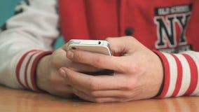 Studente sconosciuto che tiene smartphone bianco argento video d archivio