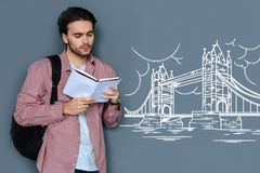 Studente serio che sembra attento mentre leggendo un libro Fotografie Stock