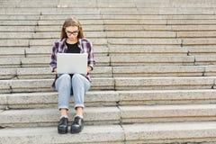 Studente serio che si siede sulle scale facendo uso del computer portatile Fotografie Stock