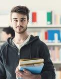 Studente sicuro che posa nella biblioteca Fotografia Stock