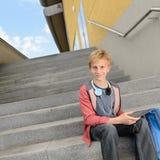 Studente sicuro con la compressa che si siede sui punti Immagini Stock