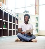 Studente sicuro With Digital Tablet in biblioteca immagini stock libere da diritti