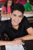 Studente Smiling While Sitting della High School allo scrittorio Immagine Stock Libera da Diritti