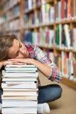 Studente sonnecchiante che si siede sul pavimento delle biblioteche che si appoggia mucchio dei libri Immagine Stock