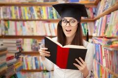 Studente sorpreso Reading della scuola un libro in una biblioteca Fotografie Stock