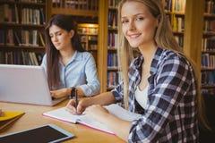 Studente sorridente che lavora nella biblioteca Fotografia Stock