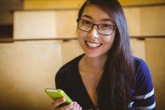 Studente sorridente che manda un sms nel corridoio di conferenza Fotografia Stock Libera da Diritti
