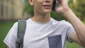 Studente sorridente che parla sul telefono in istituto universitario, sistemando data, amico aspettante archivi video