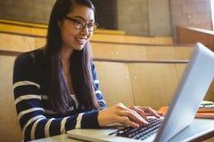 Studente sorridente che per mezzo del computer portatile Fotografia Stock