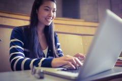 Studente sorridente che per mezzo del computer portatile Fotografie Stock Libere da Diritti