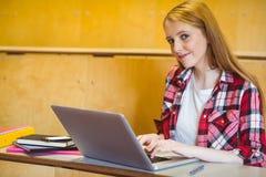 Studente sorridente che per mezzo del computer portatile durante la classe Fotografia Stock