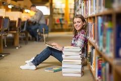 Studente sorridente che per mezzo del computer portatile sul pavimento delle biblioteche che esamina computer portatile Fotografia Stock