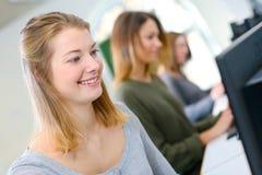 Studente sorridente che per mezzo del pc durante la classe all'università Fotografia Stock